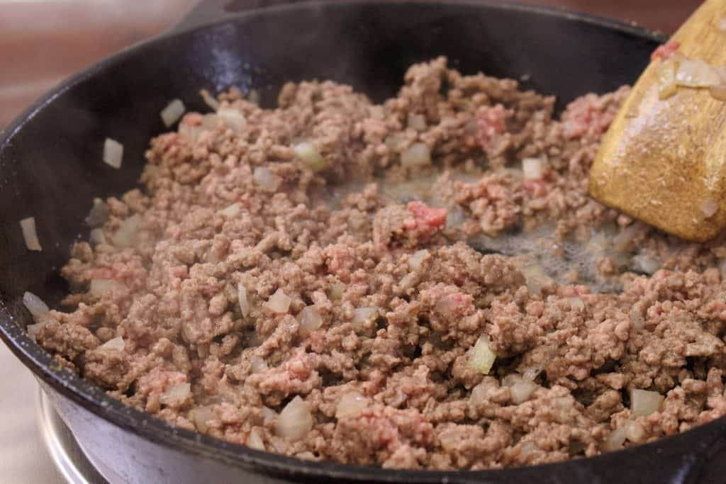 Ground beef and onions being cooked in a cast iron pan with a wooden spoon.