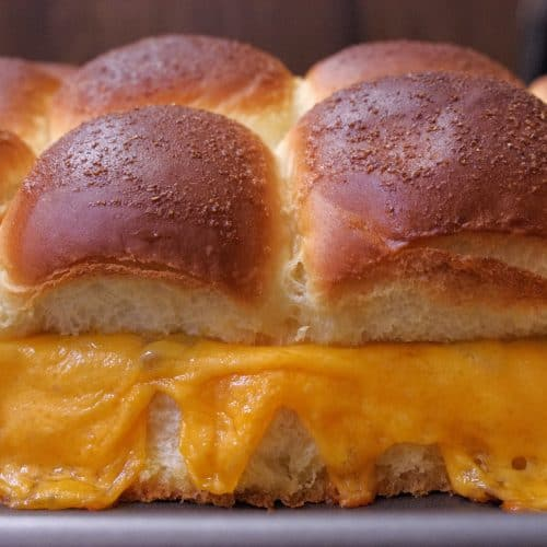 Slider rolls with melted cheese spilling over the sides