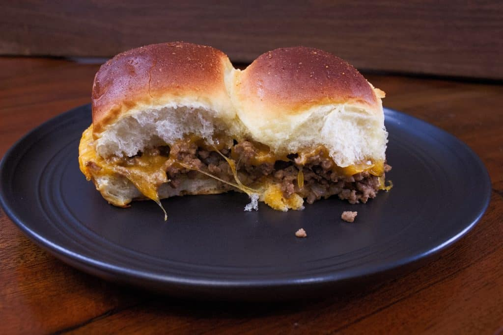 Two sliders filled with meat and cheese on a gray plate on a table