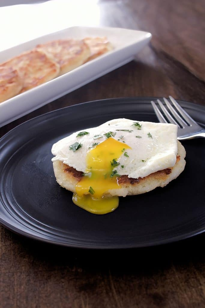 arepa with a fried egg on top where the yolk has been cut an is runny.