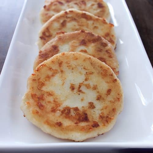 Four arepas placed in a row on a white plate on top of a wooden table