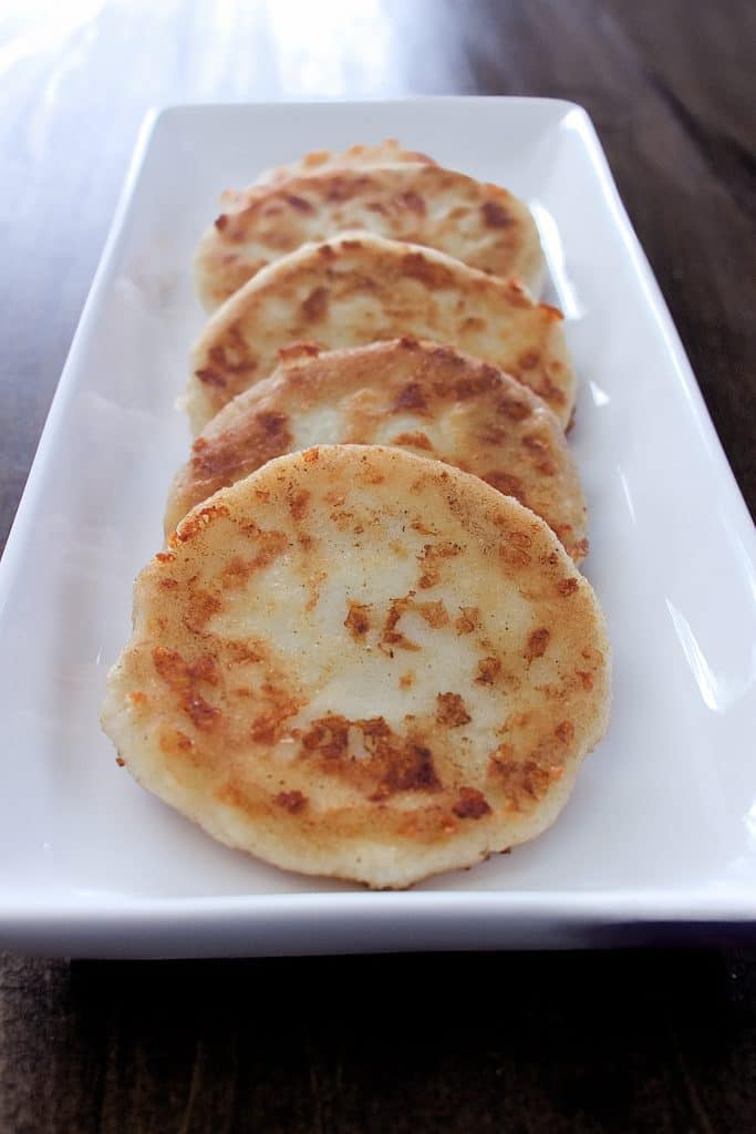 four arepas laid out evenly on a white plate