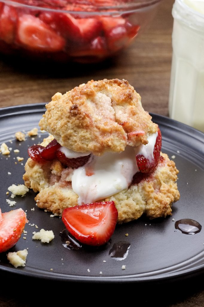 strawberry shortcake on top of a dark plate with strawberries and cream in the background